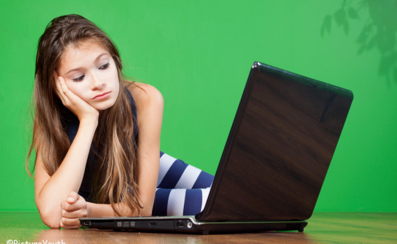 photo of teenage girl using laptop